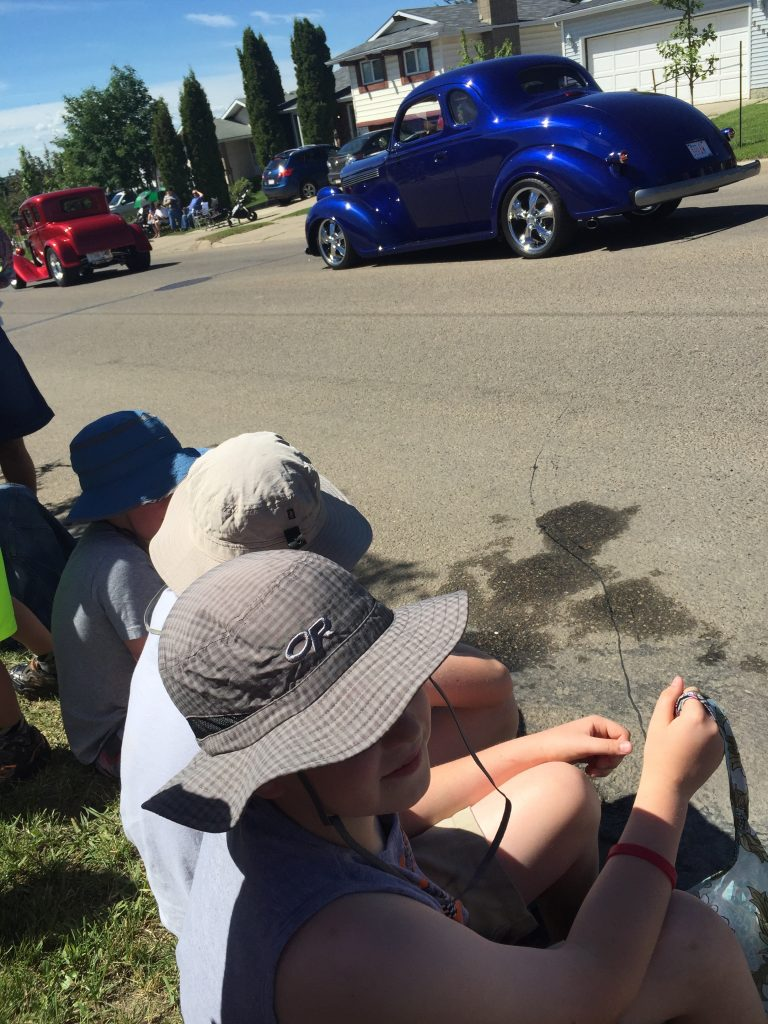 Kids sitting on the curb waiting for candy? Old cars? Check and check!