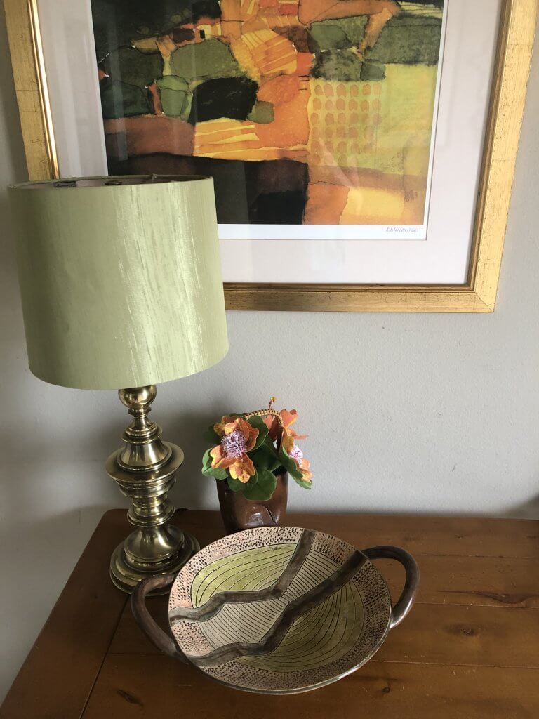 Photo of a thrifted lamp and green lampshade, bowl and vase with thrifted artwork on a thrifted entryway table.