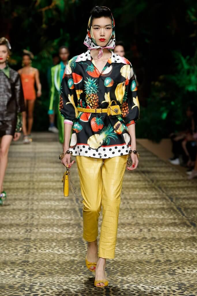 Dolce and Gabbana Summer 2020 runway look featurng fruit and polka dot print top and yellow pants