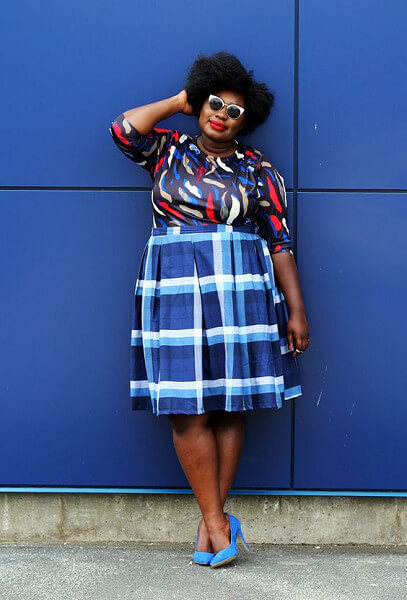 The Lion Hunter wearing a printed top with plaid blue skirt. Looking fine.