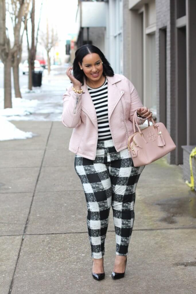 Plus size blogger wearing striped shirt, plaid pants and blush pink jacket and bag.