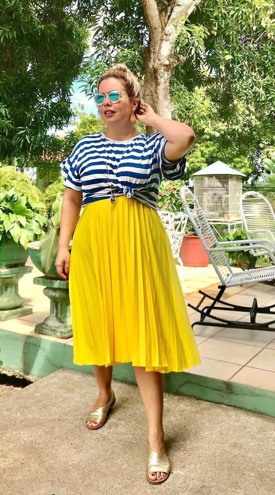 Woman wearing a mustard midi skirt with gold slides and a blue striped top to answer the question: are stripes still in style in 2020?