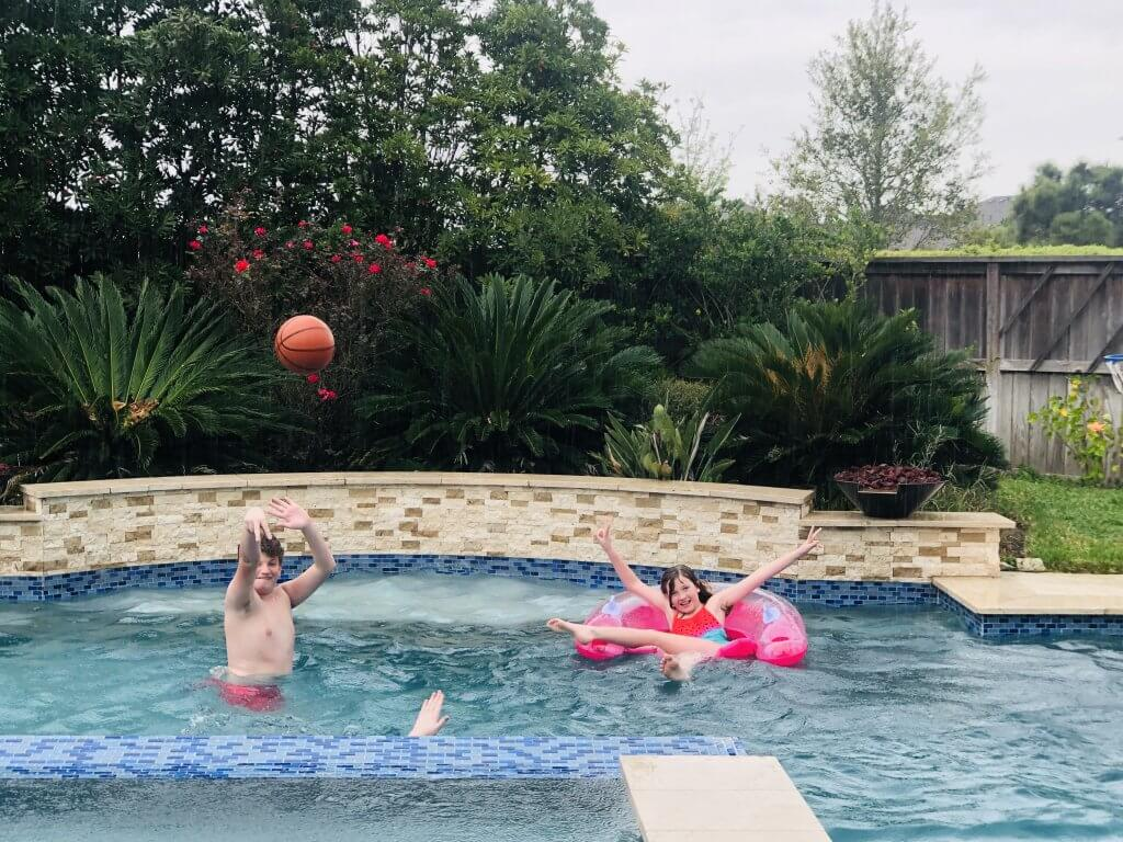 Kids playing at home in the pool, part of the Hunkering at Home Plan